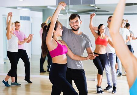 Gelukkige vrolijke positieve mensen van verschillende leeftijden die dansles hebben in de klas