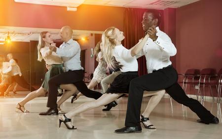 Adult dancing couples enjoying tango in dance studio