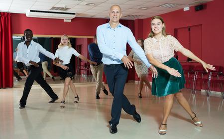Adult dancing couples enjoying rhythmic tap dance in dance studio
