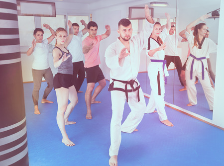 Young adult trainees practicing new maneuvers at a karate class