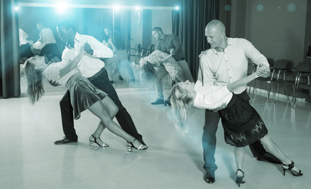 Adult dancing couples enjoying latin dances in modern studio