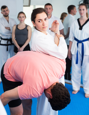 Young woman coach demonstrating painful hold to adults in taekwondo class Archivio Fotografico