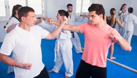 Adultos entrenando en parejas para practicar nuevos movimientos en la clase de karate. Foto de archivo