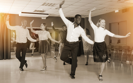 Adult dancing couples enjoying rhythmic tap dance in dance studio