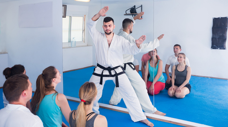 Male karate instructor shows the techniques of adult students in the classroom