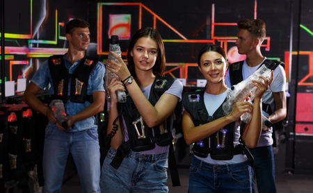 Two young women standing and holding guns during laser tag game with men in dark labyrinth Reklamní fotografie