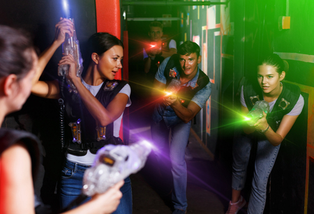 Portrait of active young friends standing with laser guns during laser tag game in dark room Standard-Bild - 122306707