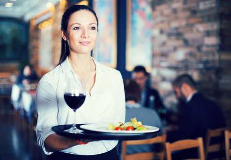 Cheerful young waitress standing with tray with glass and salad in restaurant