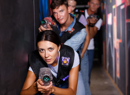 Group happy emotional people with laser guns  playing laser tag  game together in dark corridor