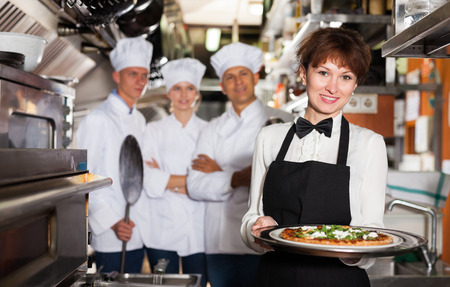 Smiling waitress standing in restaurant kitchen with ordered pizza, ready to serving guests