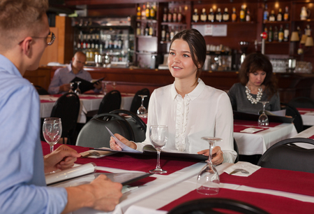 Elegant young woman sitting with menu at table in restaurant, communicating with male friend Imagens