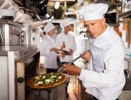Skilled male chef in white uniform working in professional kitchen of restaurant, baking ordered pizza 写真素材