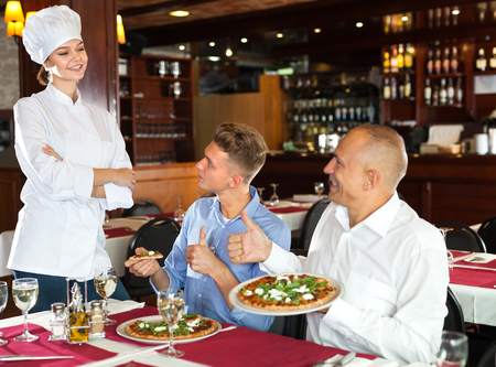 Delighted guests lauding young female chef while enjoying pizza in cozy restaurant