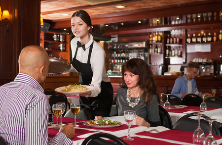 Young attractive waitress serving meals to elegant couple visited restaurant for lunch