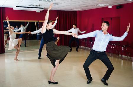 Jonge gelukkige vrolijke positieve mensen dansen rock-and-roll in paren Stockfoto