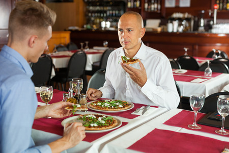 Portrait of adult man with male colleague eating pizza at lunch in cozy modern restaurant
