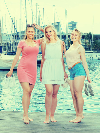 three young women standing on harbor sidewalk in european town on summer day Stockfoto