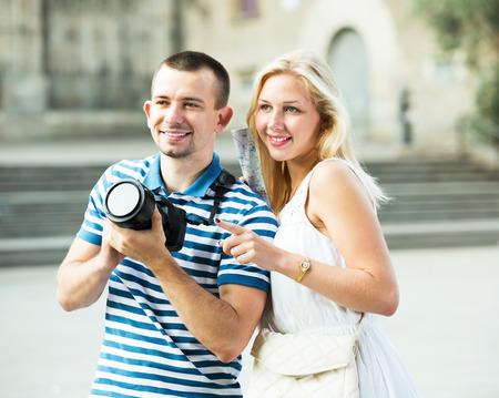 Young glad couple traveling in town and taking picture with camera