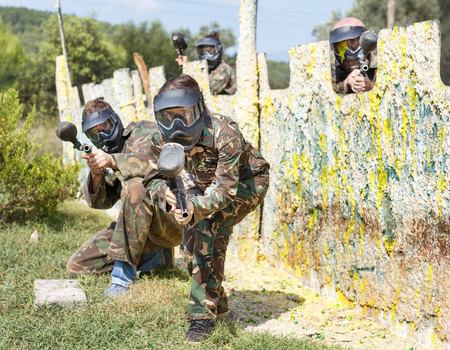 Expressive paintball team running with a marker guns at open playing field