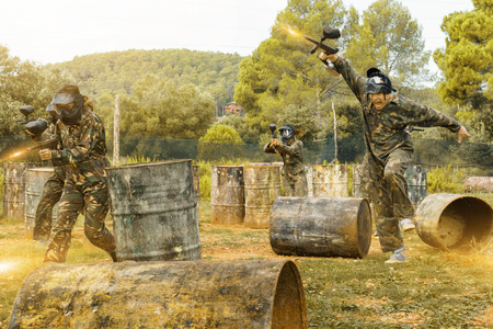 Team of happy  smiling adult people playing paintball on battlefield outdoor, running with guns