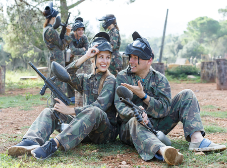 Portrait of man and woman paintball players in camouflages with masks and marker guns in forest