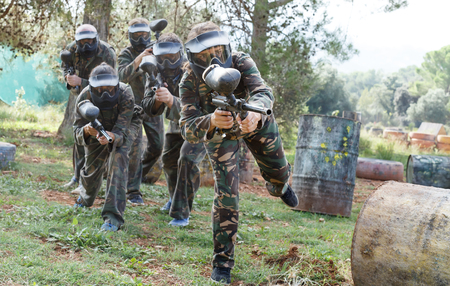 Dynamic paintball battle outdoors. Group of players in full paintball equipment attacking opposite team