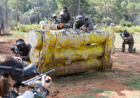 Portrait of  opposing teams in  camouflage playing  paintball  against each other outdoors 写真素材