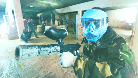 Portrait of blue team happy cheerful positive player who is aiming in opponents on paintball field. Stock Photo