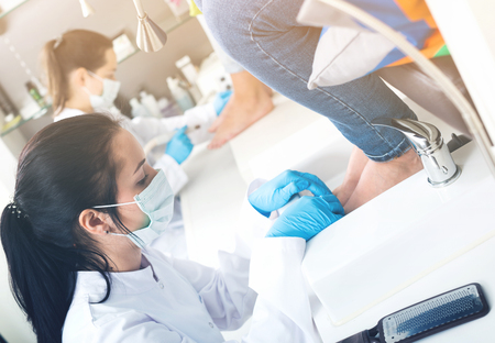Nail pedicure technician performing procedure for foot care in beauty salon
