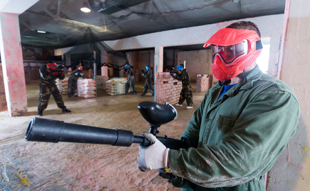 Portrait of gamer in red mask who is targeting in opponents in battlefield.