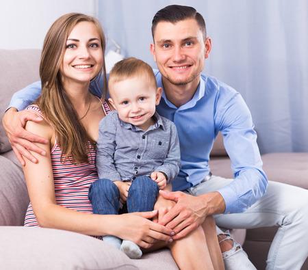 Jonge moeder en vader met zoontje glimlachend samen binnenshuis