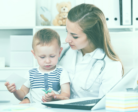 Doctor woman is examining child in clinic. 版權商用圖片