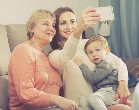 Two women and toddler are resting together and taking selfie at home.