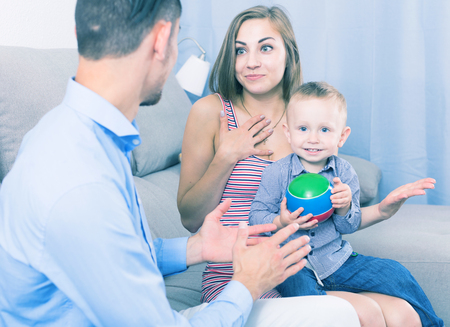 Positive wife and cheerful husband with little child talking in room