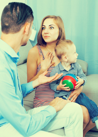 Smiling mother and father with little son talking together indoors 版權商用圖片