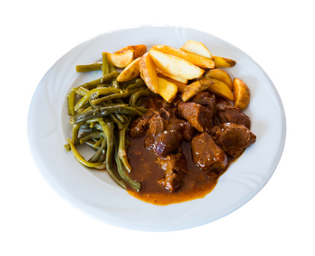 Delicious veal stew served with pickled wild garlic with fried potatoes. Isolated over white background