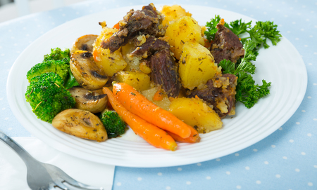 Portion of stewed beef with vegetables and fresh greens