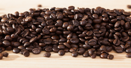 Natural background of roasted coffee beans on light wood surface Foto de archivo - 122744387