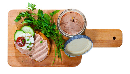 Top view of toast with meat pate, fresh cheese and vegetables served on wooden cutting board. Isolated over white background