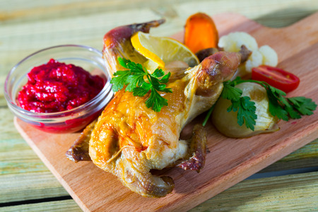Poultry dish baked in oven exquisitely served with cranberry sauce and grilled vegetables Stock Photo