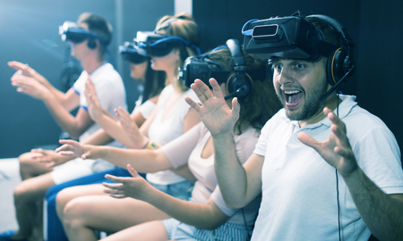 Man is enjoying exciting movie with friends in VR glasses in entertainment room. Stock fotó