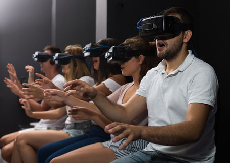Young people immersed in virtual reality with the help of 3d glasses Фото со стока