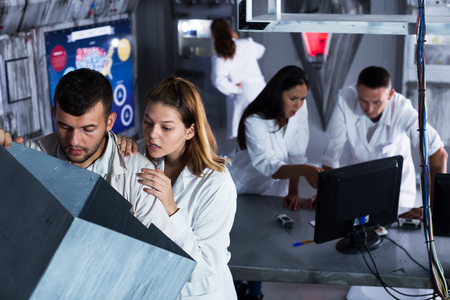 Young people solving different conundrum in escape room in view as abandoned lab