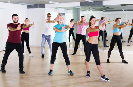 cheerful people dancing aerobics at lesson in the dance class