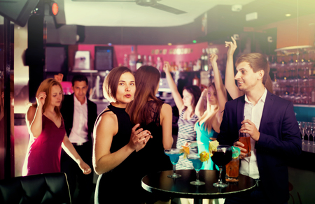 Students have fun on party with cocktails in the club