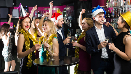 Portrait of young happy females and males in caps and garlands in the night club 스톡 콘텐츠