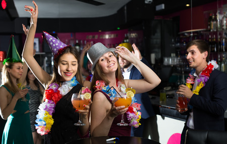 Portrait of active women and men in caps with cocktails in the night club