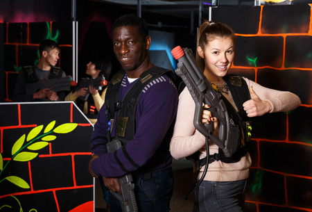 multiracial couple standing back to back holding laser guns during lasertag game on dark labyrinth
