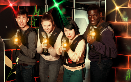 Happy adult people of different nationalities with laser pistols posing together on dark laser tag labyrinth