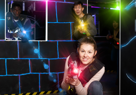 Young girl aiming laser gun at other players during lasertag game in dark room